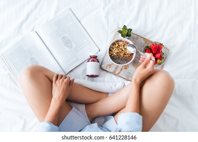 Young woman eating healthy breakfast in bed