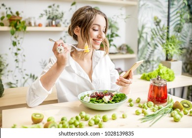 Young woman eating healthy food sitting with smartphone in the beautiful interior with green flowers on the background