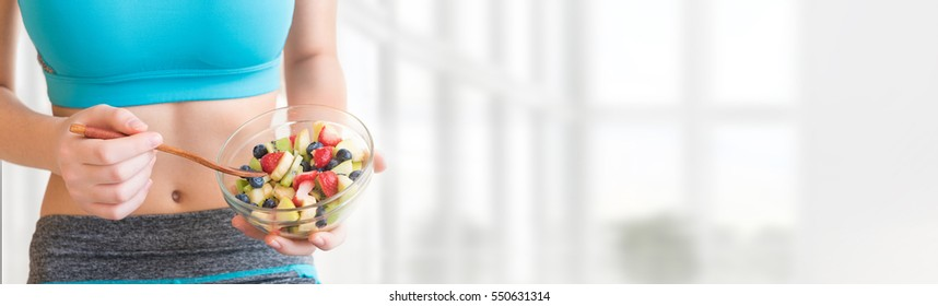 Young woman eating a healthy fruit salad after workout. Fitness and healthy lifestyle concept.
