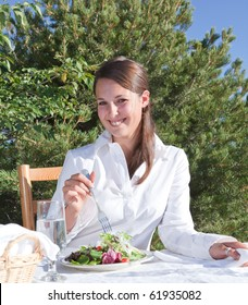 Young woman eating a healthy salad outdoors on restaurant patio