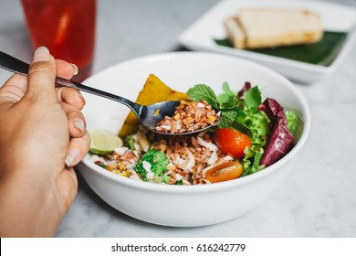 Young woman eating healthy vegetable bowl with brown rice and pumpkin, salad, tomatoes served on marble table. Lunch, dinner at cafe, restaurant