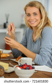 young woman eating her french breakfast: healthy food concept
