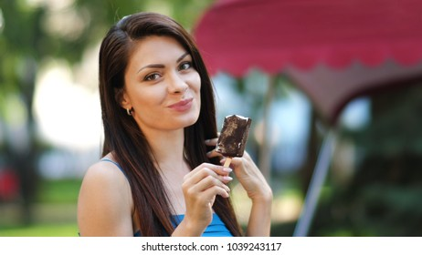 Young woman eating a ice cream on a stick