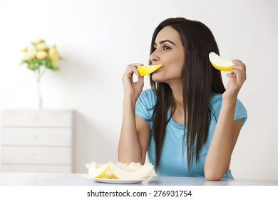Young woman eating melon at home