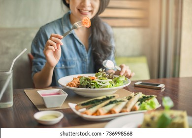 Young woman eating mixed salad in dining table. Young and happy woman eating healthy salad sitting on the table.