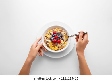 Young woman eating muesli cereal breakfast with berry fruit in a white bowl viewed directly from above. Female hand holding a spoon with fresh rich in fiber granola dish viewed from above. Top view.