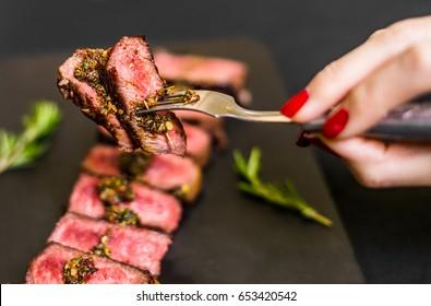 Young woman eating new york strip porterhouse steak meat