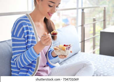 Young woman eating oatmeal in living room