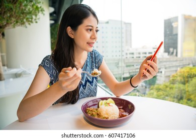 Young woman eating Pad Kra Pao Moo at restaurant and texting message on smartphone using social media share information with friends always connect online internet.