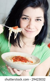 Young woman eating pasta in the kitchen