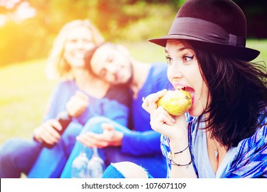young woman eating a pear and having picnic with two friends