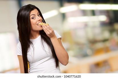 Young Woman Eating Piece Of Granula Bar, Indoor