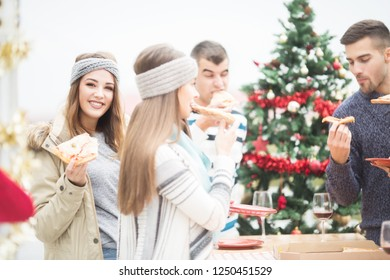 Young woman eating Pizza with friends on balcony for Christmas