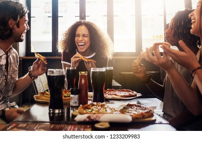 Young woman eating pizza and laughing while sitting with her friends in a restaurant. Group of friends enjoying while having food and drinks at cafe.
