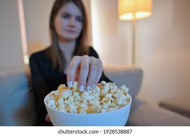 Young Woman Eating Popcorn on sofa