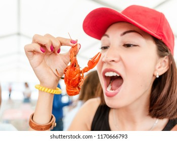 Young woman eating red boiled delicious crayfish or crawfish river lobster. Local cuisine and seafood concept