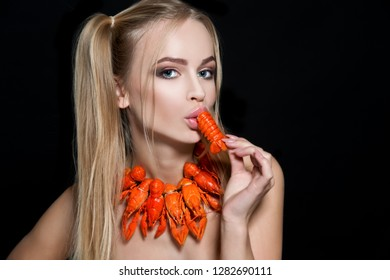 Young woman eating red boiled delicious crayfish or crawfish river lobster. Local cuisine and seafood concept. Beauty portrait.