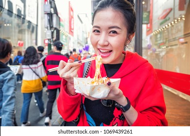 Young woman eating Roasted lobster with cheese at Myeong-dong street food in Seoul, South Korea