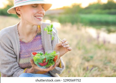 Young woman eating salad with beautiful landscape
