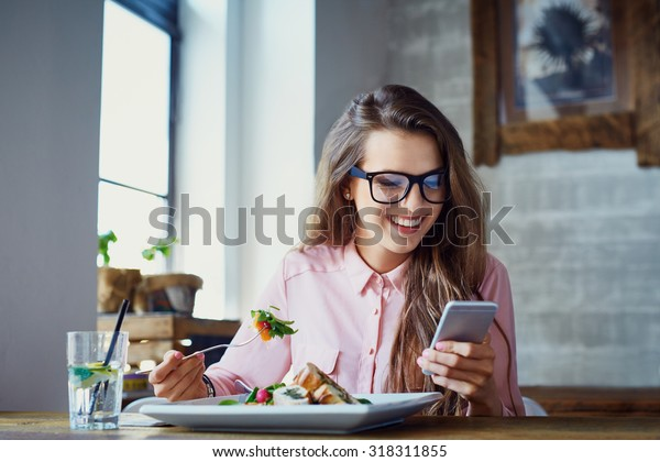 Young woman eating salad at restaurant and texting on smartphone