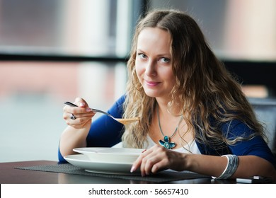 Young woman eating soup.