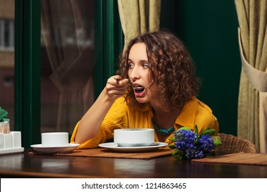 Young woman eating a soup at restaurant Stylish fashion model with brown curly hairs wearing yellow shirt