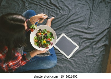 Young woman eating summer salad with vegetables and flowers nasturtium and violets sitting on bed, top view. Copy space