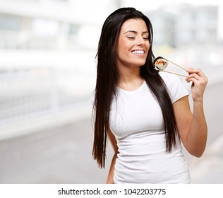 young woman eating a sushi piece, outdoor