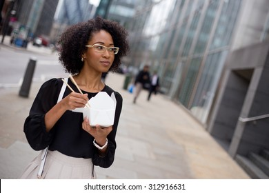 young woman eating a take-away in the city