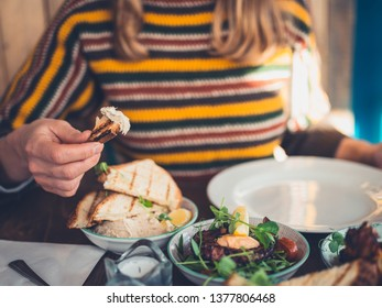 A young woman is eating tapas in a restaurant