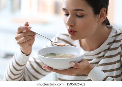 Young woman eating tasty vegetable soup indoors