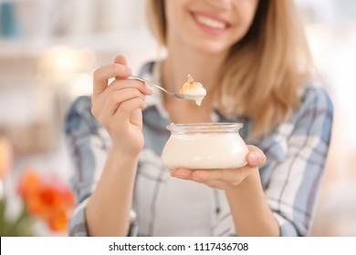 Young woman eating tasty yogurt, closeup
