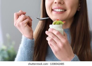 Young woman eating tasty yogurt at home, closeup