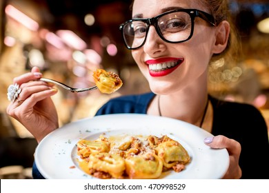 Young woman eating tortellini pasta in front of the food shop in Bologna. Tortellini ring-shaped pasta was invented in Bologna.