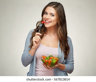 young woman eating vegetable salad. studio isolated portrait. girl with long hair.