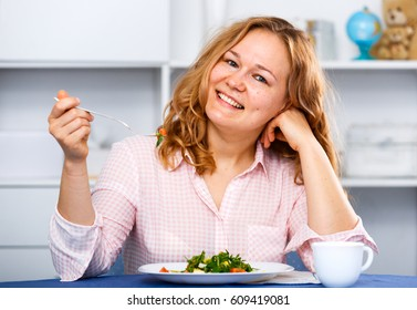 Young woman eating vegetarian salad for diet and healthy lifestyle