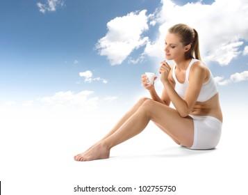 Young woman eating yogurt as breakfast or snack