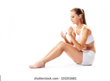 Young woman eating yogurt on white background