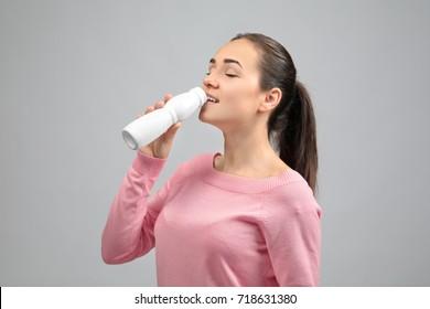 Young woman eating yogurt on light background
