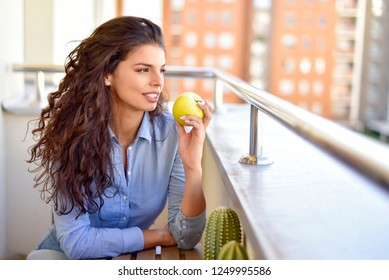 Young woman eats an apple