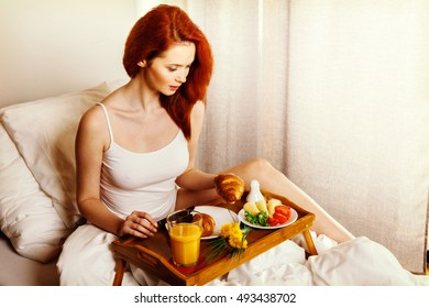 Young woman eats breakfast in bed in the morning. Lifestyle concept. Toned image