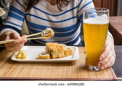 Young woman eats sushi rolls with chopsticks