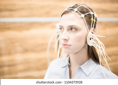Young woman with eeg electrodes all around her head having medical test of brain activity