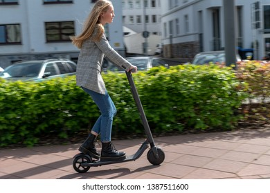 Young woman with electric scooter on a bike path in a city