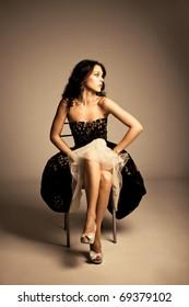 young  woman in elegant dress sit on chair, studio shot, full body shot