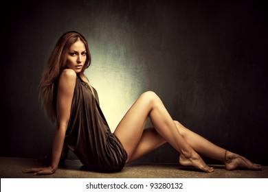 young woman in elegant short dress sit  barefoot, full body shot, studio shot