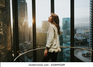 Young woman in a elevator at window  enjoying the city skyline from the 35 floor, at sunset, with stunning panoramic view of Los Angeles.