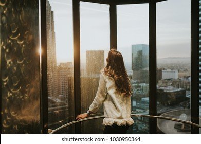 Young woman at elevator window, enjoying the city skyline from the 35 floor, at sunset, with stunning panoramic view of Los Angeles.