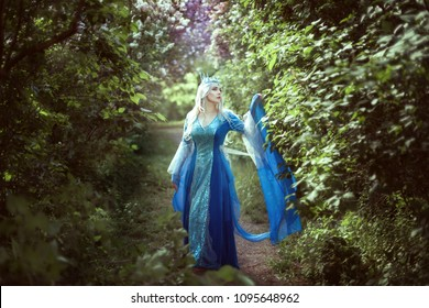 Young woman elf in a blue dress standing in a fairy forest.