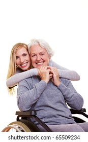 Young woman embracing disabled elderly woman in wheelchair